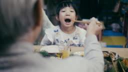 Japanese grandfather feeding grandchildren on New Year's Eve