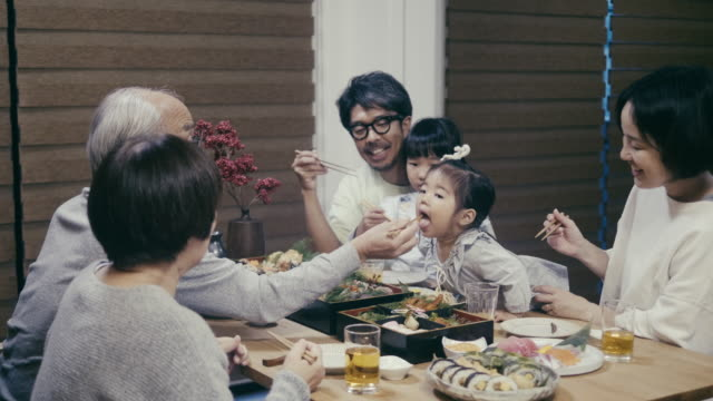 vídeos de stock e filmes b-roll de japanese grandfather feeding grandchildren on new year's eve - família