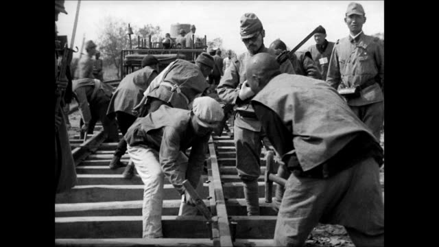 japanese guards soldiers w/ bayonet ws chinese workers aka 'coolies' working on railroad japanese guard vs coolies prisoners hammering tracks ms... - prisoner of war stock videos & royalty-free footage