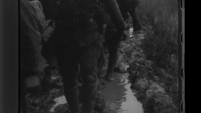 Japanese Imperial Army infantrymen carrying machine guns advance through mud and cross a river to attack enemy pillboxes under a smokescreen
