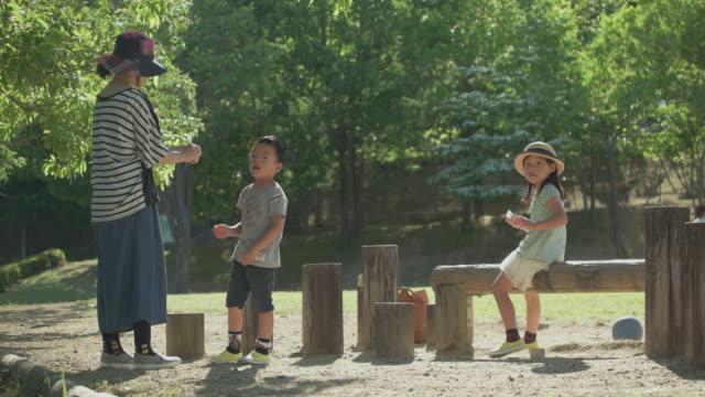 vídeos de stock, filmes e b-roll de japanese kids having fun in the park. - família de duas gerações