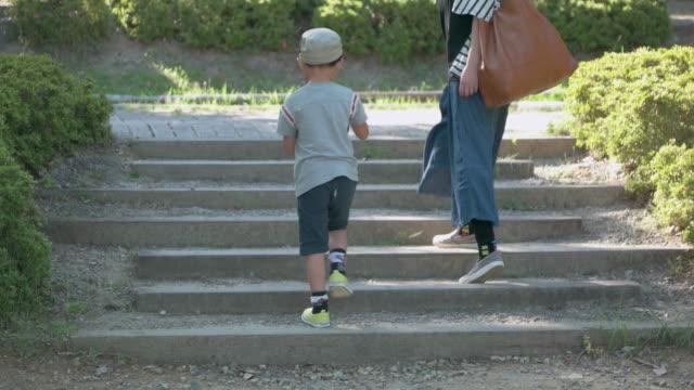 vídeos y material grabado en eventos de stock de japanese kids walking with mother in the park. - parque natural
