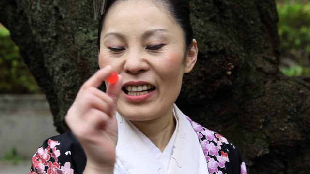 japanese kimono woman eating a candy - only mature women stock videos & royalty-free footage