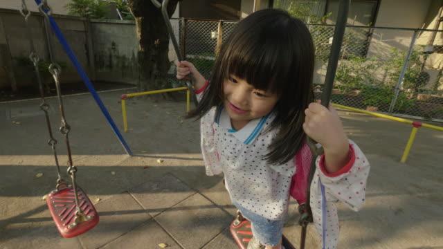 japanese little girl on swing set - 校庭点の映像素材/bロール