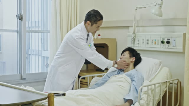 Japanese Male Doctor checking Male Patient at hospital ward