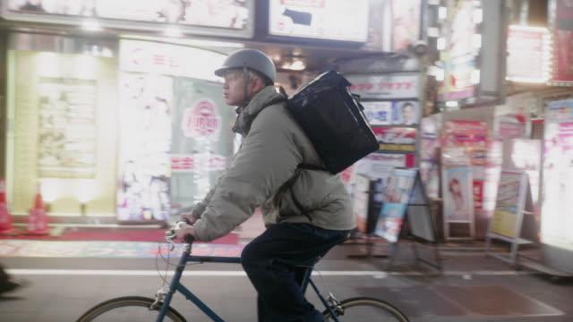 東京で食べ物を配達する日本の男性食宅配業者(スローモーション) - 配達員点の映像素材/bロール