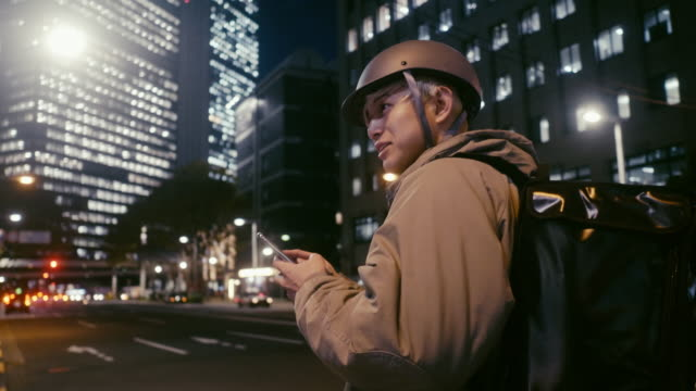 japanese male food courier looking for the delivery address - helmet stock videos & royalty-free footage