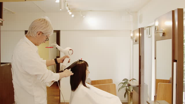 japanese male hairdresser is drying wet hair of japanese woman with a hair dryer at a hairdresser - wet hair stock videos & royalty-free footage