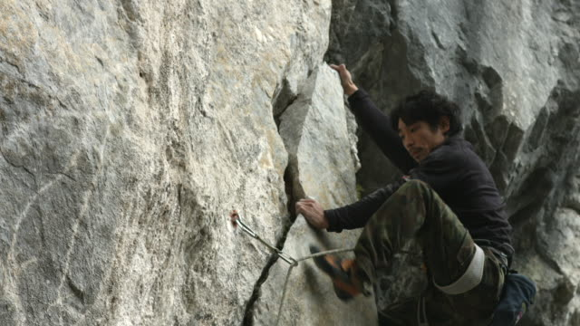 a japanese male rock climber climbs a limestone rock face - 挑戦点の映像素材/bロール