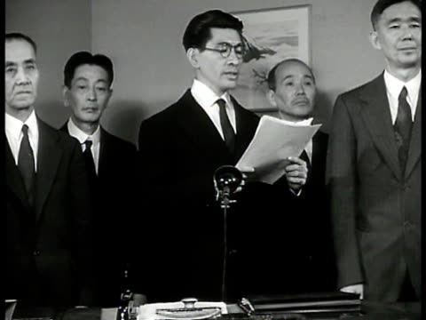 reprisal japanese male standing behind desk w/ others making speech saying japan working in 'harmony w/ italy nazi germany' the us 'too weak too... - 映像撮影点の映像素材/bロール