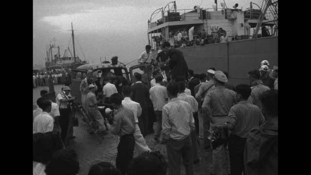 japanese man carried down gangplank of ship, united states military police and photographer standing on dock / man on stretcher coming down the... - 囚人点の映像素材/bロール
