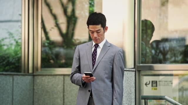 japanese man checking cell phone - portability点の映像素材/bロール