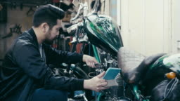Japanese man fixes his motorcycle while watching tutorials on digital table