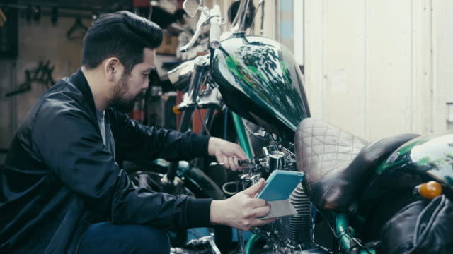 japanese man fixes his motorcycle while watching tutorials on digital table - diy stock videos & royalty-free footage