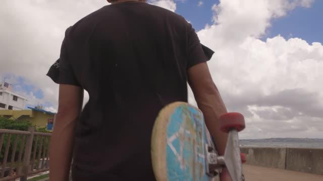 vídeos y material grabado en eventos de stock de japanese man hold skateboard walking by the ocean. - gorra de béisbol