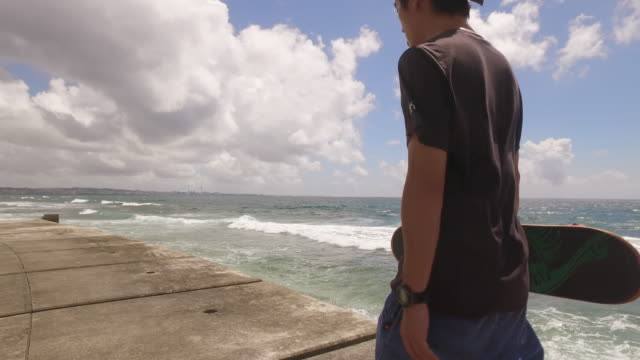 Japanese man hold skateboard walking by the ocean.