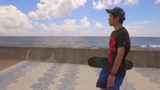 Japanese man hold skateboard walking.