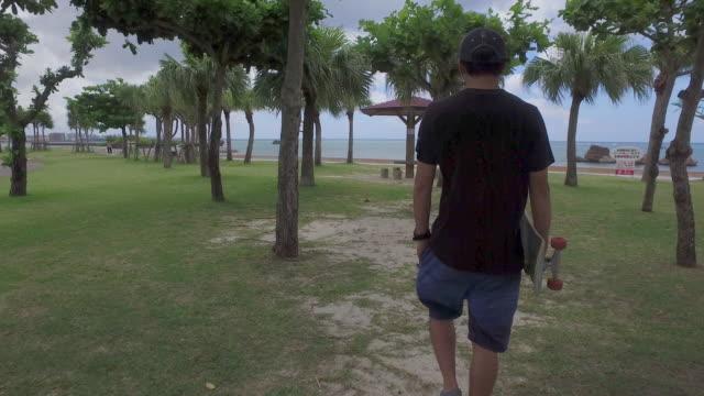 japanese man hold skateboard walking. - medium shot stock videos & royalty-free footage