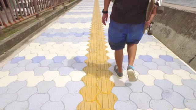vídeos de stock, filmes e b-roll de japanese man hold skateboard walking. - paralelepípedo