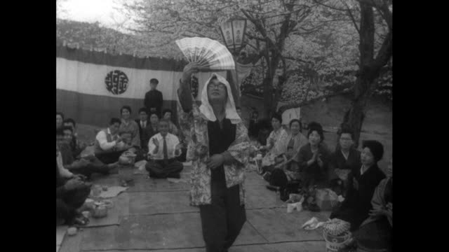 japanese man imitates dancing geisha woman; 1962 - bbc archive stock-videos und b-roll-filmmaterial