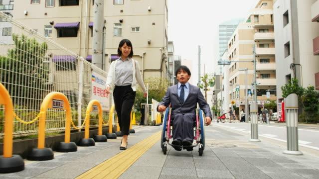 vídeos y material grabado en eventos de stock de hombre japonés en silla de ruedas - adversidad