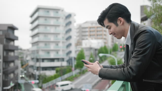 japanese man in early 20s using phone on outdoor terrace - railings stock videos & royalty-free footage