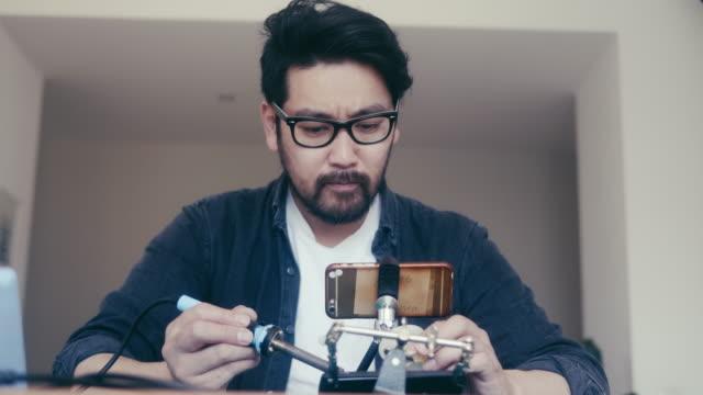 自宅でスマートフォンを修理する方法をユーチューブから学ぶ日本人男性 - 日曜大工点の映像素材/bロール