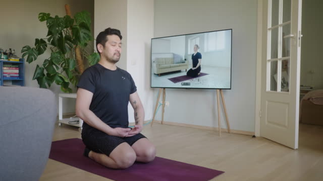 japanese man meditates during a yoga online session at home - mindfulness stock videos & royalty-free footage