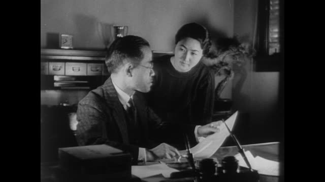 japanese man notarizes document in office while smiling woman stands beside him in the us during wwii - guerra del pacifico video stock e b–roll