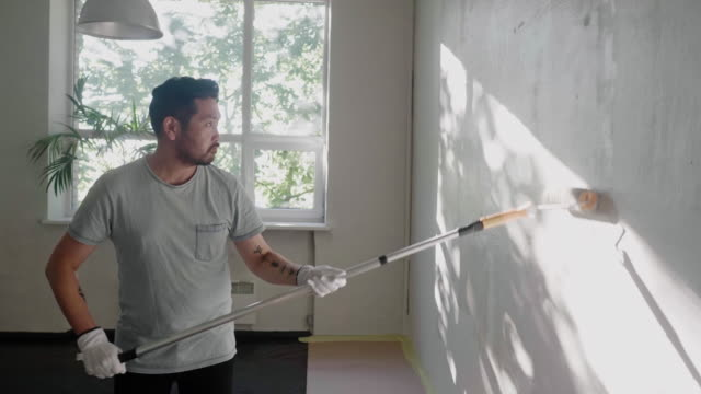 japanese man paints the wall at home with paint roller - loft apartment stock videos & royalty-free footage