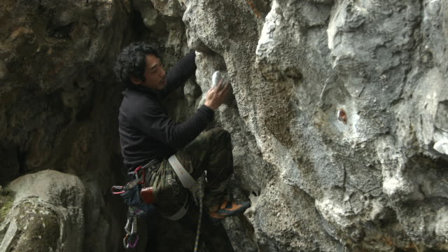 a japanese man rock climbing - rock face stock videos & royalty-free footage