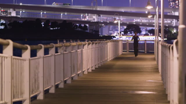 ms a japanese man runs next to tokyo bay / tokyo, japan - vest stock videos & royalty-free footage