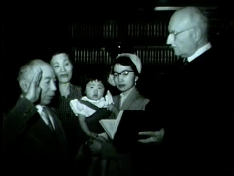 vidéos et rushes de japanese man takes and oath in front of an american judge and his family in chicago in 1953 - 1953