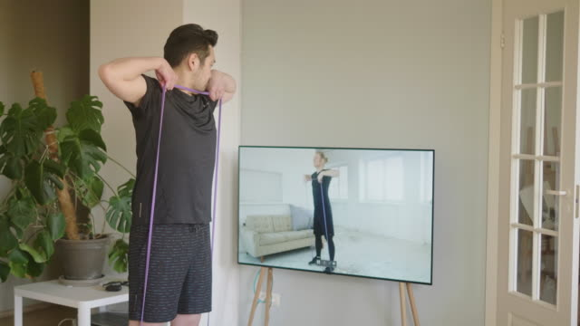japanese man taking online resistance band fitness lessons during lockdown in isolation - sportswear stock videos & royalty-free footage