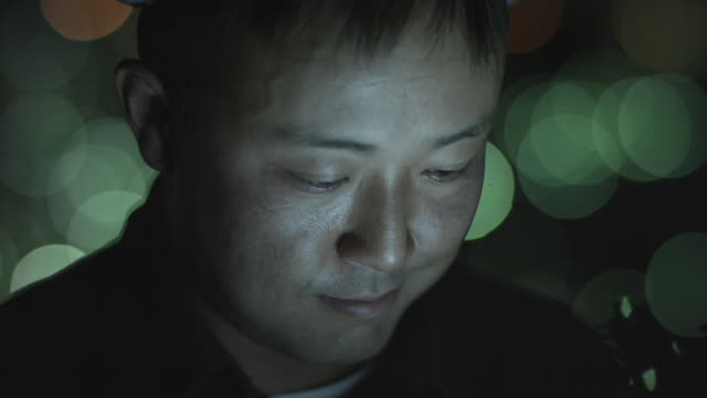 A Japanese man using a tablet computer at night