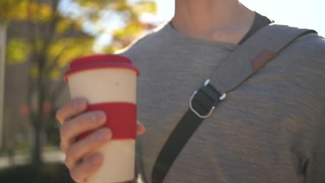 japanischer mann, der mit einer wiederverwendbaren kaffeetasse in der hand herumläuft. - cup stock-videos und b-roll-filmmaterial