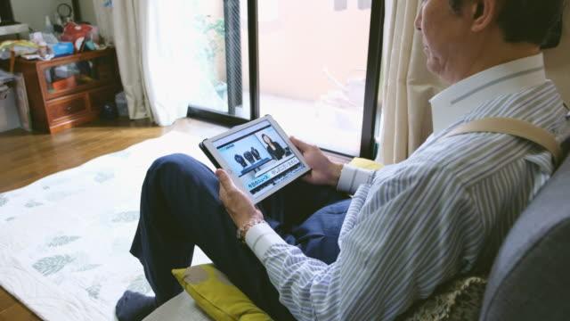 stockvideo's en b-roll-footage met japans man kijken online nieuws - presentator media