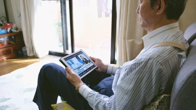 日本男は見てのオンライン ニュース - mature adult点の映像素材/bロール