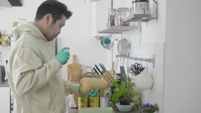 vídeos de stock e filmes b-roll de japanese man wearing protective gloves disinfects food with spray - epidemiologia