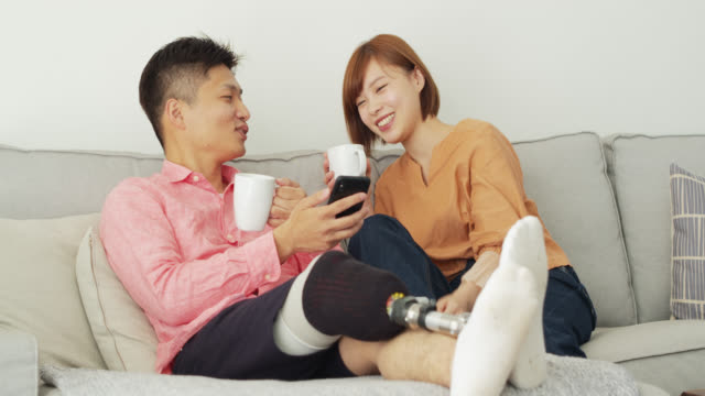japanese man with prosthetic leg drinking coffee with girlfriend at home - artificial limb stock videos & royalty-free footage