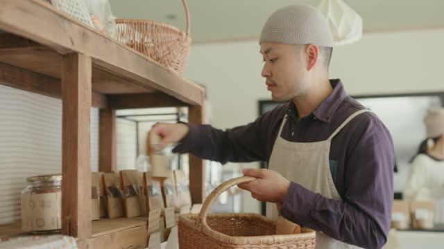 持続可能な店で働くms-日本人男性が棚を補充 - マネージャー点の映像素材/bロール