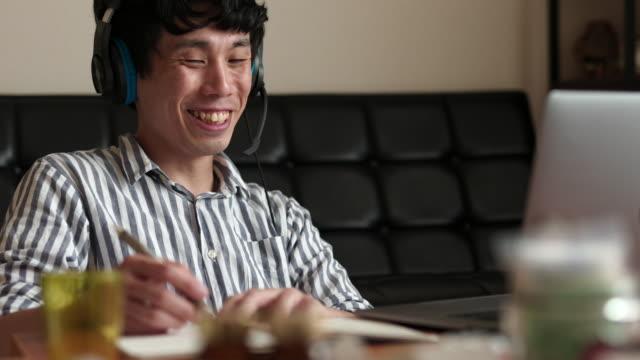 居間で遠隔で働く日本人男性がビデオ会議中にメモを取る - マルチタスク点の映像素材/bロール