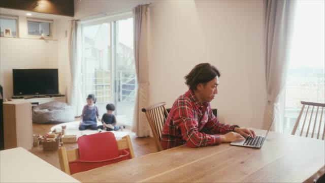 vidéos et rushes de l'homme japonais travaille à la maison tandis que les enfants jouent dans le salon - famille de deux générations