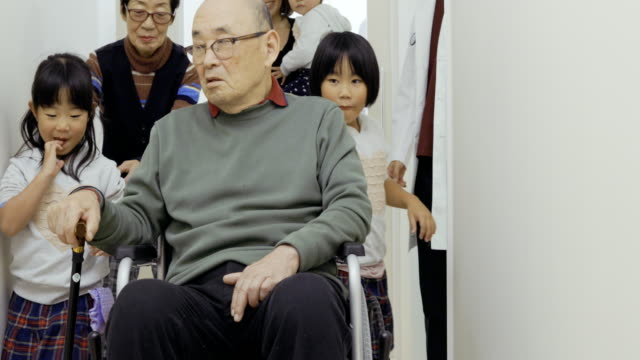 vídeos y material grabado en eventos de stock de japanese medical system.patient coming from the examination room with wheelchair.family pleased to leave the hospital. - silla de ruedas trabajo