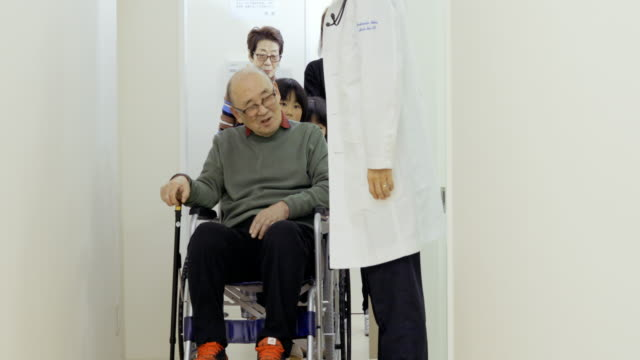japanese medical system.the doctor talking to the patient coming from the examination room with wheelchair. - leaving hospital stock videos & royalty-free footage