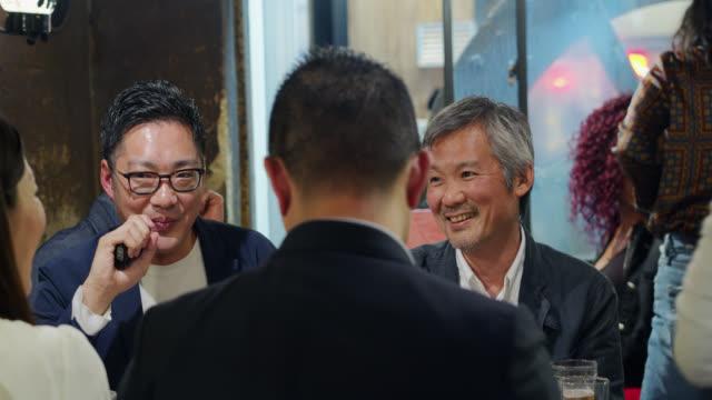 仕事の後に混雑したバーで飲む日本人男性 - 居酒屋点の映像素材/bロール