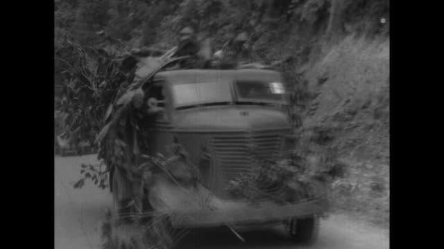 stockvideo's en b-roll-footage met japanese military tanks heavy artillery bicycle units and supply trucks cross a makeshift bridge while airplanes bombard enemy territory in singapore... - 1942
