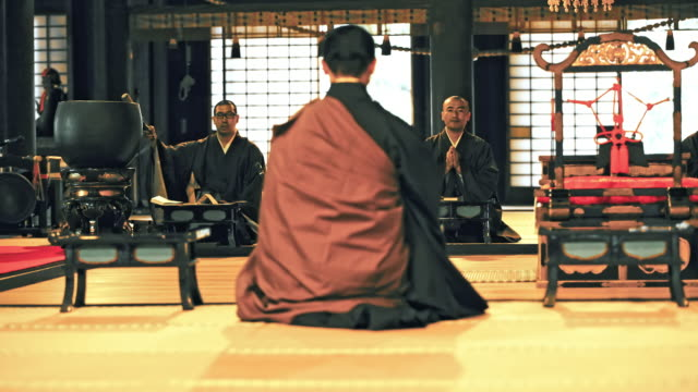 DS Japanese monks praying in a temple