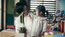 Japanese mother and daughter making New Years Eve decoration (kadomatsu)