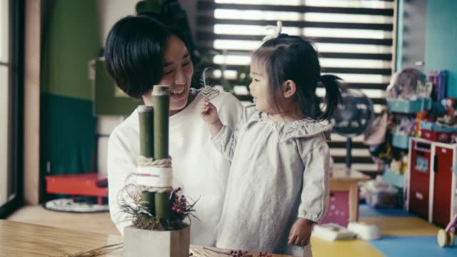 大晦日の飾り付けをする日本の母と娘(門松) - 日曜大工点の映像素材/bロール